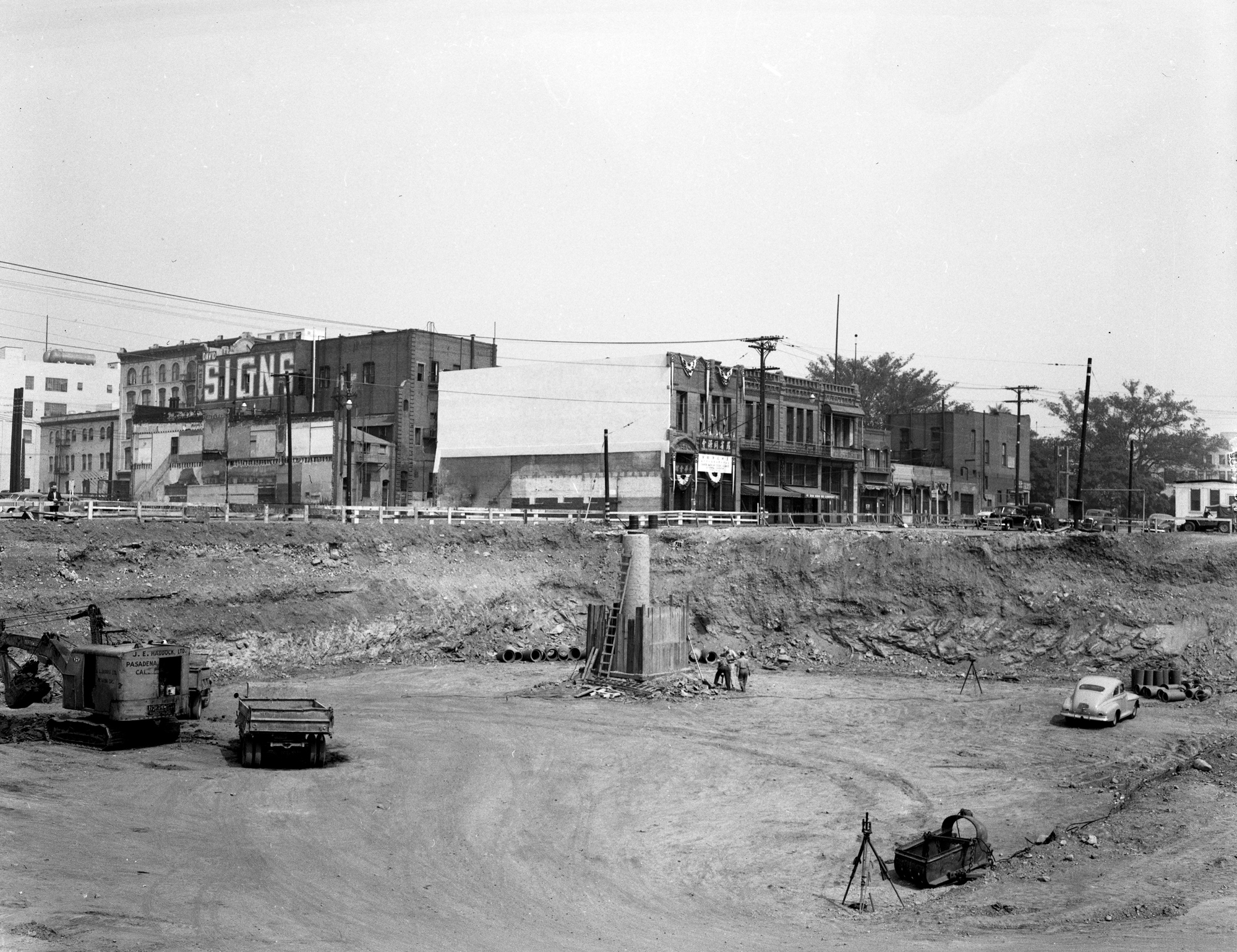 Construction of 101 Freeway after forced relocation of Old Chinatown, Garnier Building (now the Chinese American Museum) in background (1949)