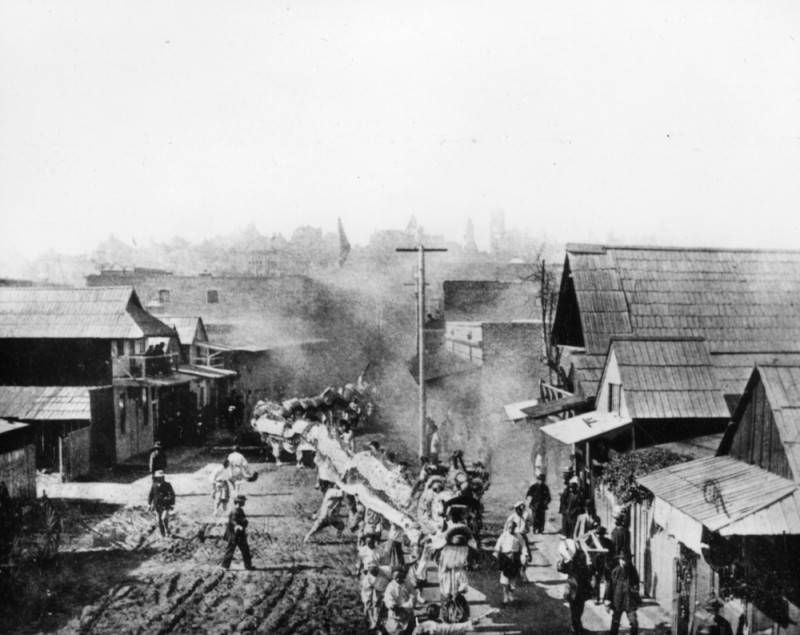 A dragon parading through the dirt streets of Old Chinatown (c. 1900)