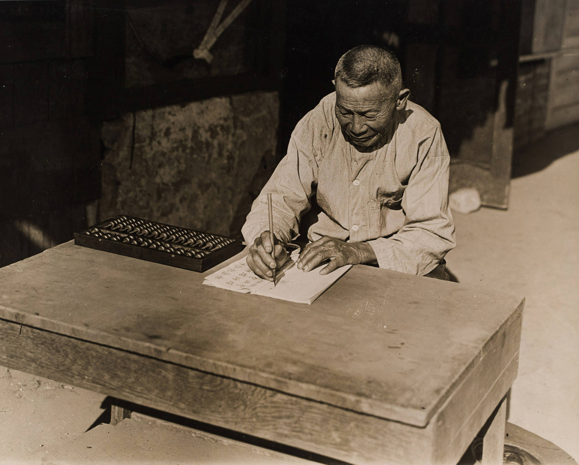Chinese merchant with abacus in Old Chinatown (1915)