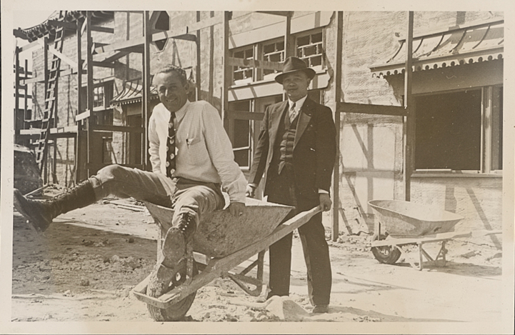 Peter SooHoo Sr. poses pushing a man in a wheelbarrow during the construction of New Chinatown (1938)