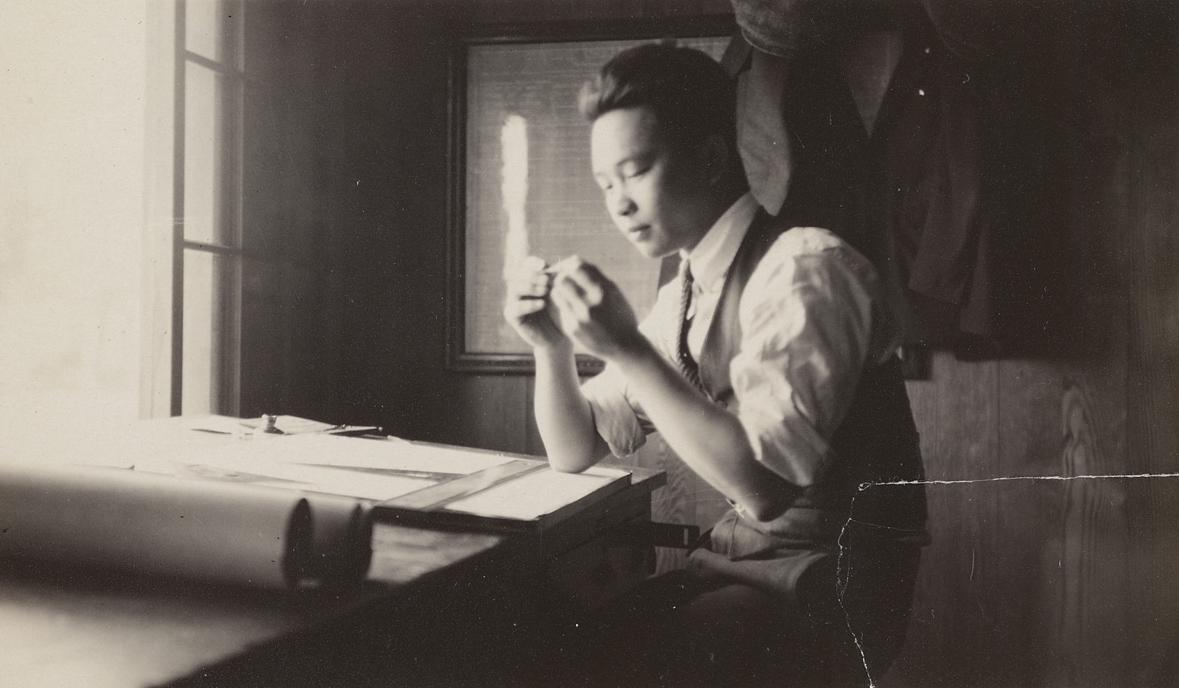 Peter SooHoo Sr. working at a drafting table (1920s)